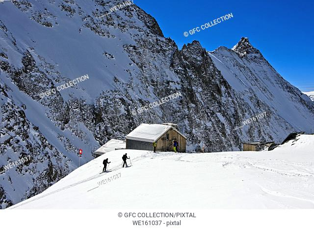 Ski tourers ariving at the mountain refuge Hollandiahütte on the Loetschenluecke pass, Blatten, Loetschental, Valais, Switzerland