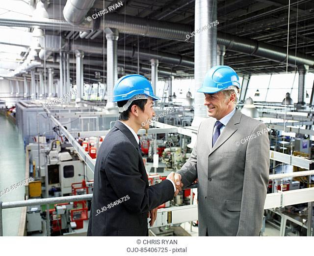 Businessmen in hard-hats shaking hands