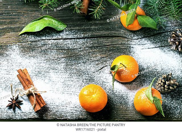 Tangerines on a wooden background with snow. Top view