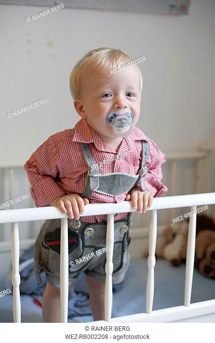Toddler with pacifier staying in his baby cot wearing traditional Bavarian leather trousers