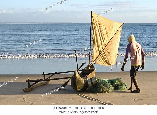 Fisherman ready to go fishing on his outrigger pirogue with sail. At Foulpointe ( Madagascar)