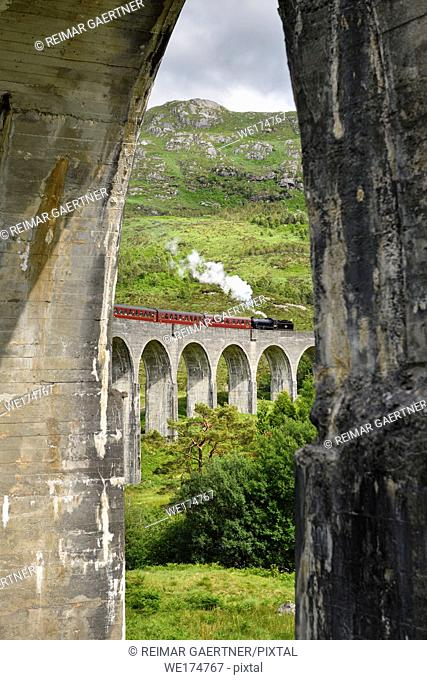 View of heritage Jacobite Steam Train through concrete columns of the Glenfinnan viaduct in the Scottish Highlands Scotland UK