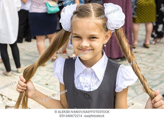 Schoolgirl at the festival on September 1 holds her long hair in her hands
