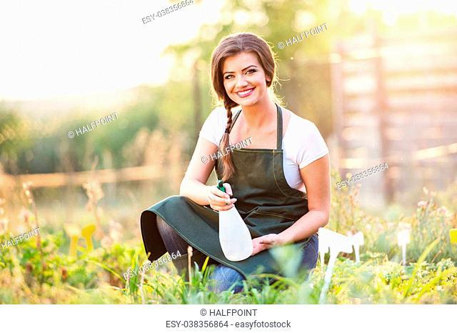 Young gardener in green apron sprinkling various plants in her garden, sunny summer nature
