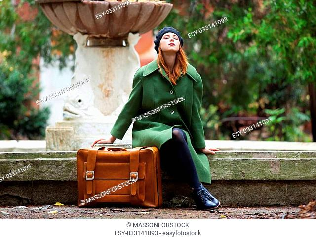Redhead girl with suitcase sitting at autumn outdoor