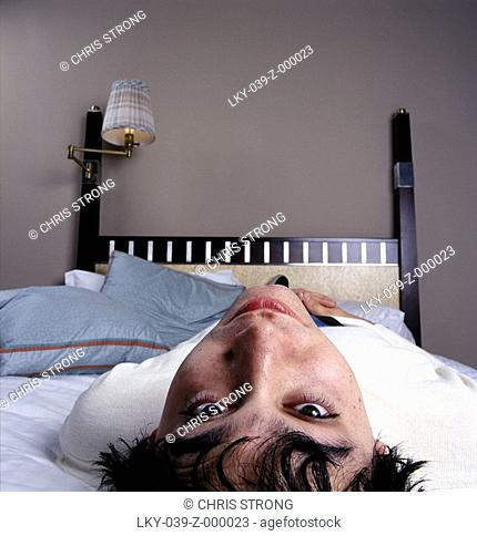 Man lying on back on bed looking at camera
