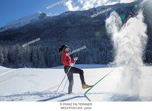 Germany, Bavaria, Inzell, female skier having fun in snow-covered landscape