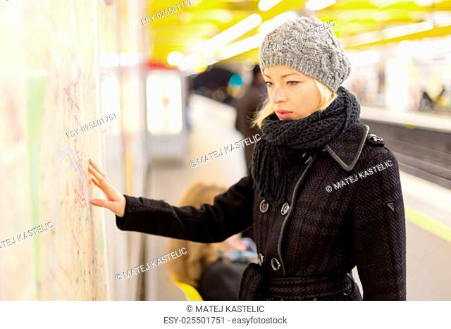 Casually dressed woman wearing winter coat, orientating herself with public transport map panel. Urban transport