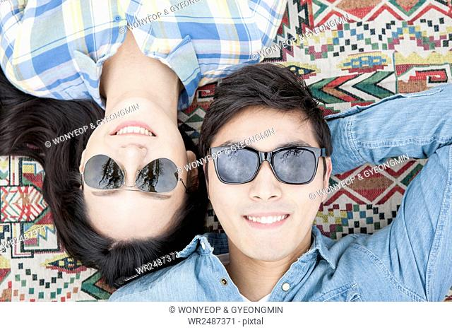 Portrait of young smiling couple with sunglasses lying down