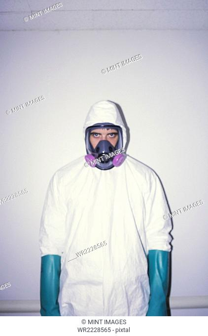 A man wearing a white protective clean suit and long thick blue gloves, and breathing mask