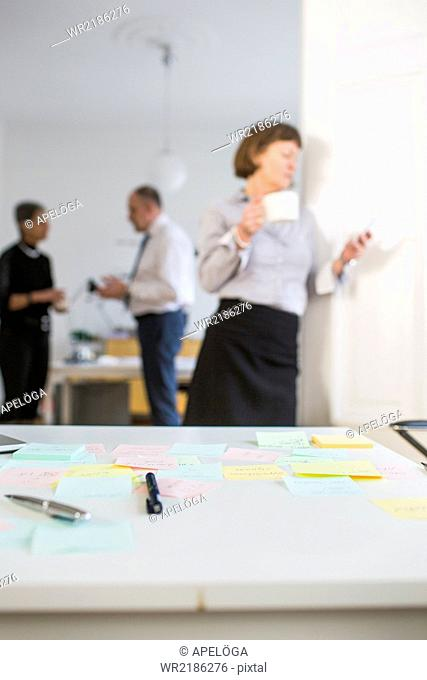Reminders and pens on desk with business people in office