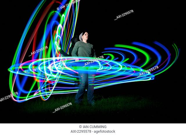 Woman spinning hula hoop lit with LEDs in field at night; West Sussex, UK