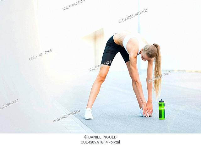 Young female runner touching toes on city sidewalk