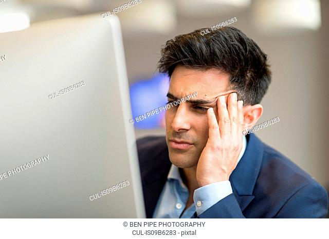 Confused businessman looking at computer in office