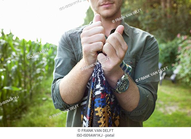 Cropped shot of mid adult man folding blanket in field