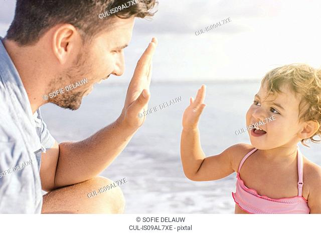 Father and toddler daughter giving high five at beach, Tuscany, Italy