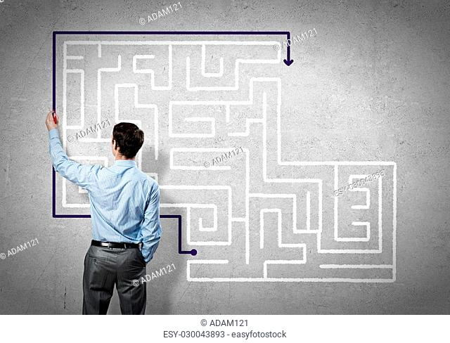 Back view of businessman drawing labyrinth on wall