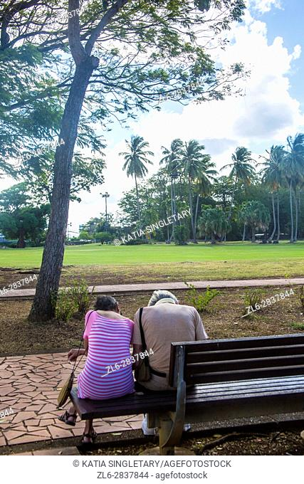 Very Old couple sitting on a bench hunch down looking at the ground  in the Beautiful colorful streets of the fun and cosmopolitain city and capital of...