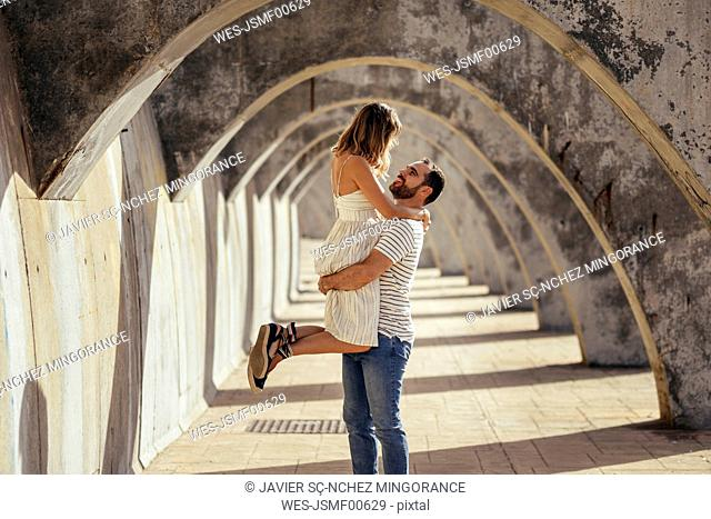 Spain, Andalusia, Malaga, happy man lifting up girlfriend under an archway in the city