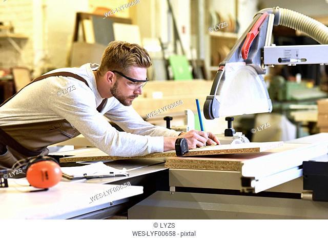 Carpenter measuring wooden boards in his workshop