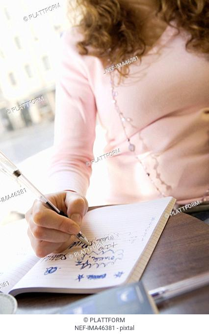 A girl writing in her note book in a café