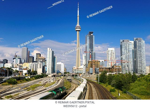 GO trains leaving on rail corridor from downtown Toronto highrise towers