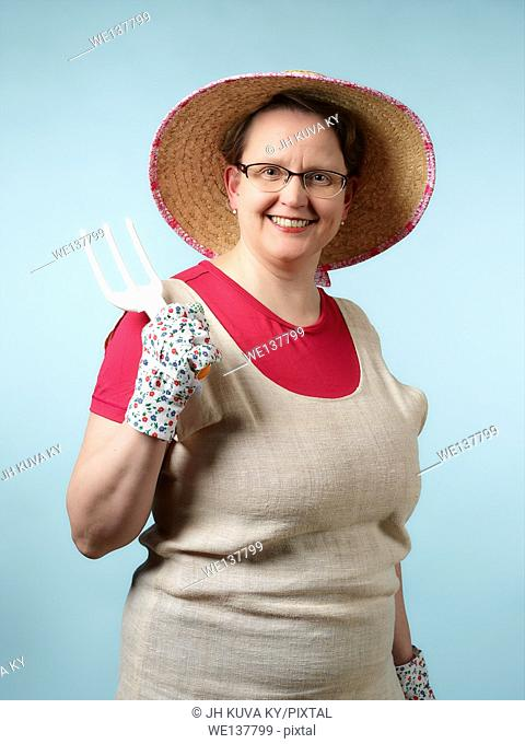 Mature woman, gardening, studio shot, light blue background