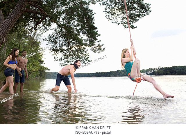 Young woman rope swinging above lake