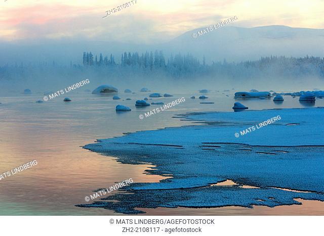 Winter landscape with fog over the river in Tjåmotis, Swedish lapland, lapland, Sweden