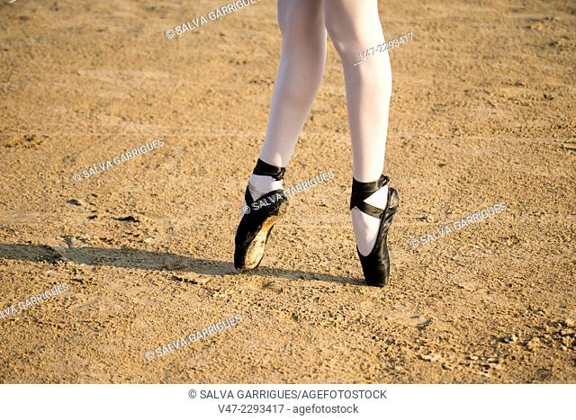 Ballet dancer dancing on the beach on toes