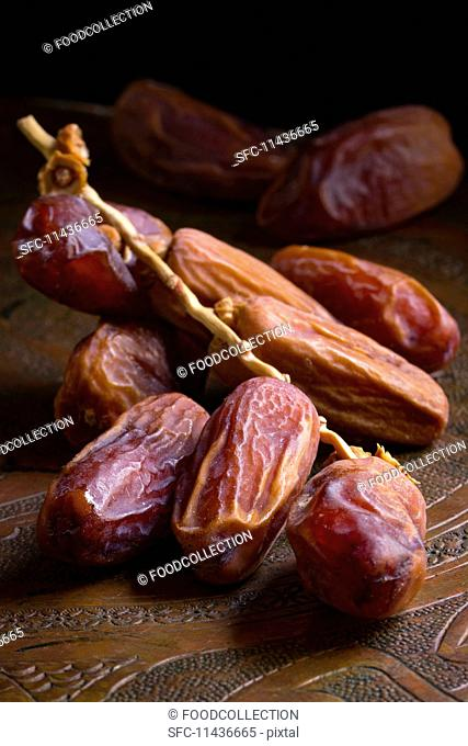 Dates with a sprig on a wooden platter