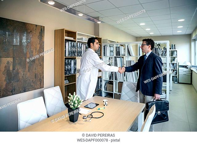 Man in suit and doctor shaking hands in medical office