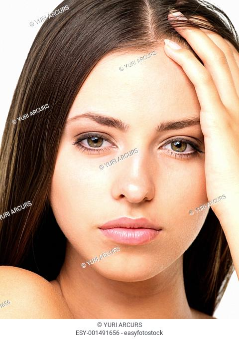 Closeup portrait of beautiful young woman with hand in hair on white background