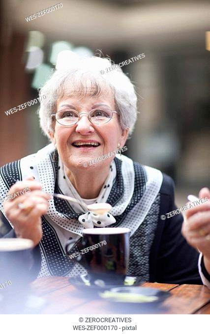 Portrait of senior woman relaxing in a pavement cafe