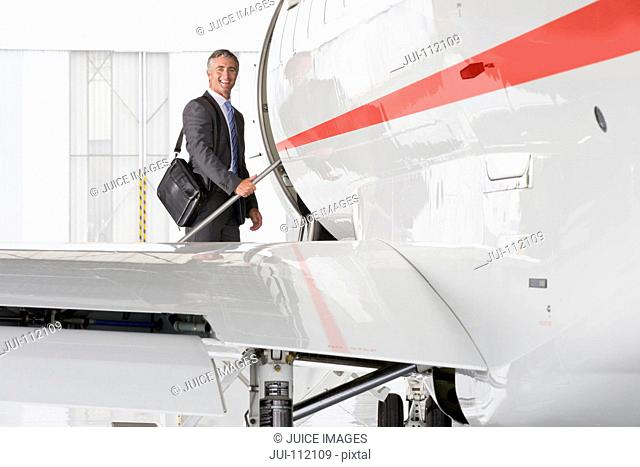 Businessman boarding private jet and smiling at camera