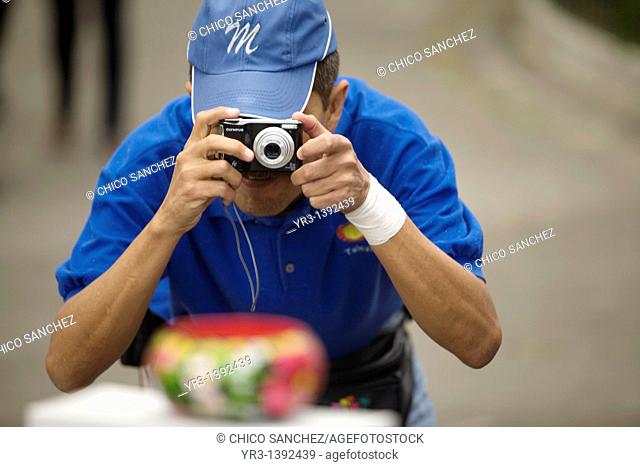 A visually impaired man takes pictures of an object
