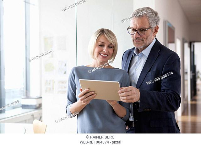 Businessman and woman having a meeting, looking at digital tablet