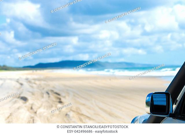 View over defocused beach with 4wd vehicle detail on the right. Vacation and tourism concept image with space for text