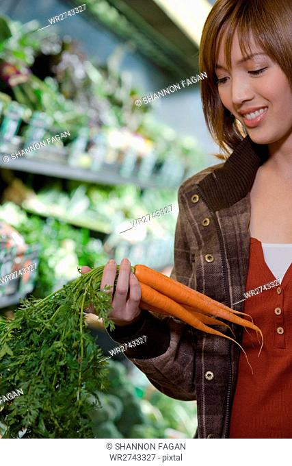 Young woman holding a bunch of carrots