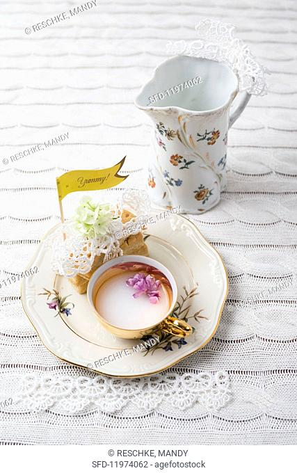 A retro place setting decorated with flowers, lace and a flag on a knitted tablecloth