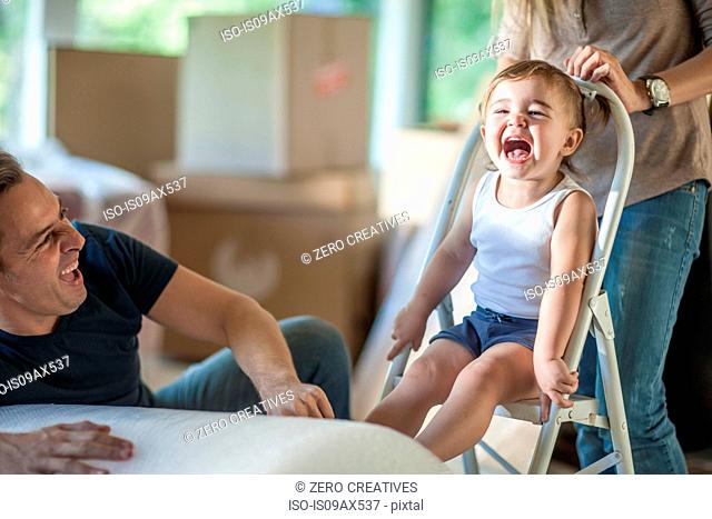 Moving house: father and daughter laughing, daughter sitting on step stool