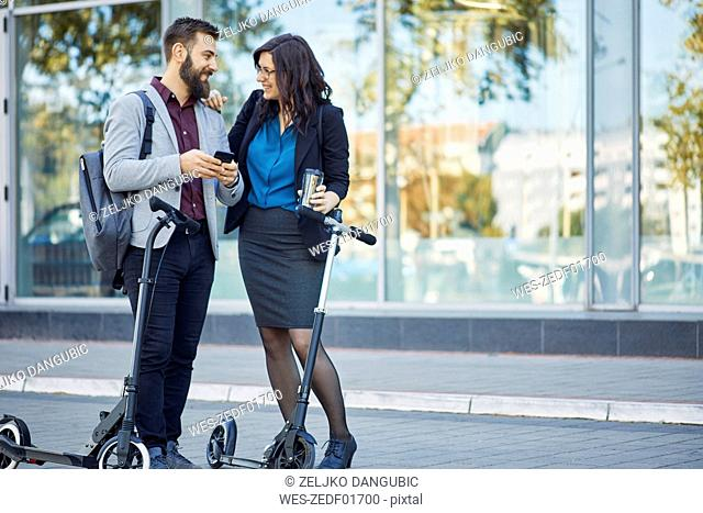 Smiling businessman and businesswoman with scooters talking on pavement