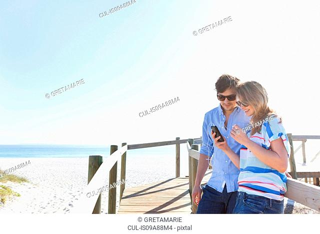 Couple on boardwalk with cell phone