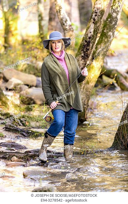 A pretty blond 59 year old woman holding a fly fishing rod near a stream in a forest