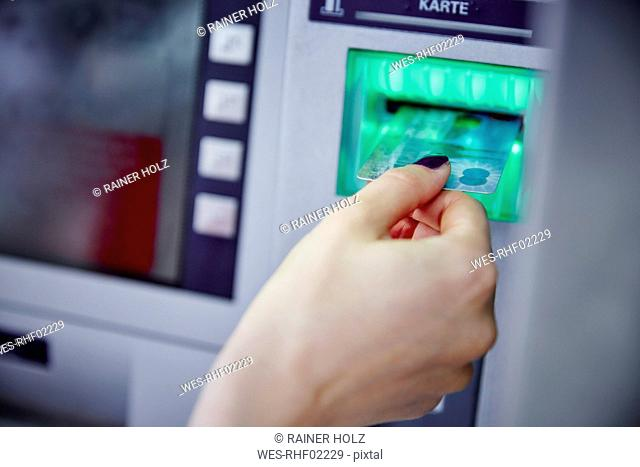 Close-up of woman putting card into slot of cash machine