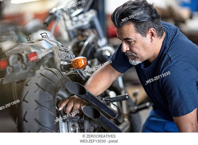 Mechanic cleaning motorcycle in workshop