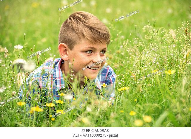 Boy lying in meadow, smiling cheerfully