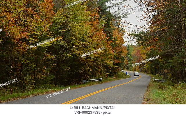 Northern Vermont mountains roads with cars traveling in fall foilage colors in beautiful fall colors