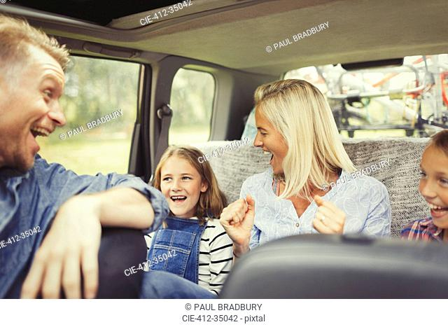Playful family laughing and singing in car