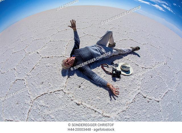 man lying on Salt lake Uyuni, biggest salt lake of South America